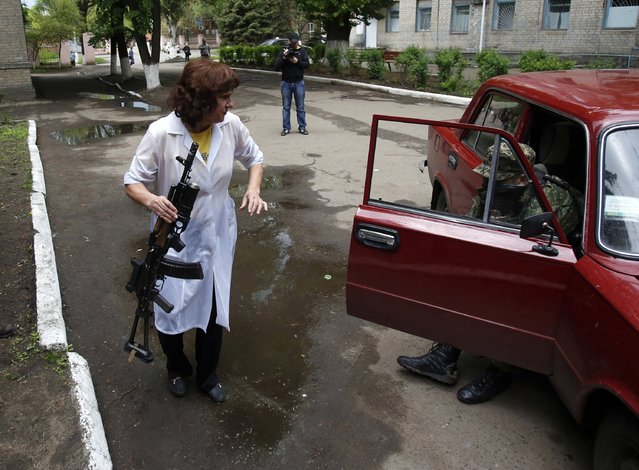 A nurse holds a gun as she helps a wounded Pro-Russian gunmen to get out of the car in front of local hospital in Slovyansk, eastern Ukraine, Monday, May 5, 2014. Ukrainian troops fought pitched gun battles Monday with a pro-Russia militia occupying an eastern city пїЅ an apparent escalation of their efforts to bring the region back under government control. (Photo by Darko Vojinovic/AP Photo)