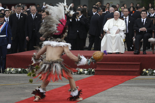 Pope Francis and Paraguay's President Horacio Cartes watch a performer during the pope's welcome ceremony at Silvio Pettirossi International airport in Asuncion, Paraguay, Friday, July 10, 2015. The Paraguay government declared Friday and Saturday national holidays in honor of the pope's visit. (Photo by Victor R. Caivano/AP Photo)