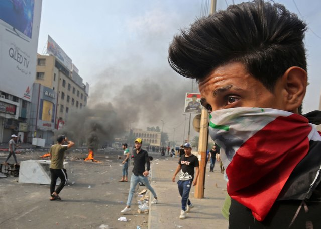 A protester wearing an Iraqi national flag as a bandana face mask stands during clashes between protesters and riot police amidst demonstrations against state corruption, failing public services, and unemployment, in the Iraqi capital Baghdad's central Tahrir Square on October 3, 2019. Iraqi security forces fired live rounds on October 3 to break up protests held for a third day in Baghdad despite an open-ended curfew in effect since dawn. The chaotic protests and ensuing clashes with riot police in Baghdad and several southern cities have left a dozen protesters and one police officer dead. (Photo by Ahmad Al-Rubaye/AFP Photo)