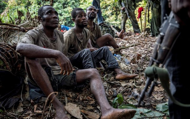Three poachers sit on the floor after being detained by park rangers in Salonga National Park, Kinshasa, Democratic Republic of the Congo, July 10, 2018. Hunting is prohibited in national parks, which means wildlife is more abundant so poachers often hunt inside the protected areas to find animals with greater ease. (Photo by Thomas Nicolon/Reuters)