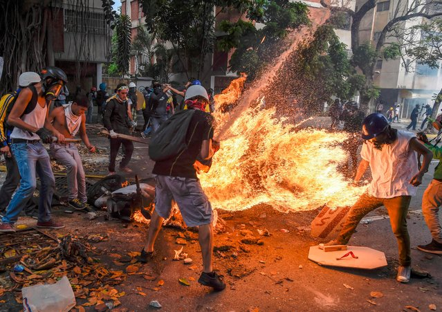 A demonstrator catches fire, after the gas tank of a police motorbike exploded, during clashes in a protest against Venezuelan President Nicolas Maduro, in Caracas on May 3, 2017. (Photo by Juan Barreto/AFP Photo)