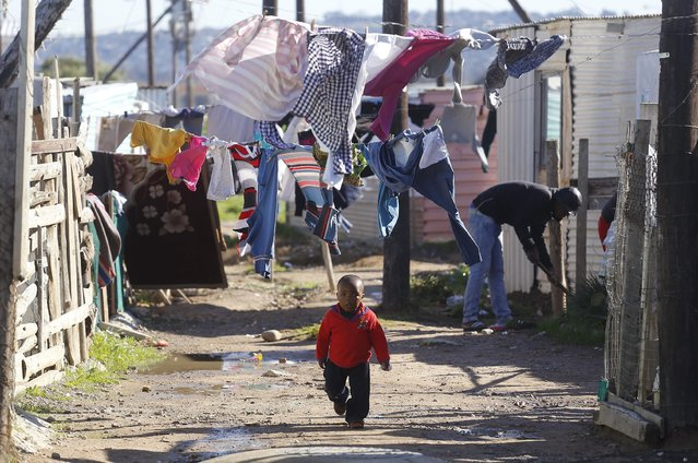 A child walk on a dirt road near his home as people nearby paint shacks with white fire retardant paint as part of their contribution to International Nelson Mandela day celebrating former South African president Mandela birth day in the township of  Nomzamo , South Africa,  Saturday, July 18, 2015. Thousands of South Africans celebrating former South African president Nelson Mandela birthday by giving 67 minutes of their time to help other people. (Photo by Schalk van Zuydam/AP Photo)