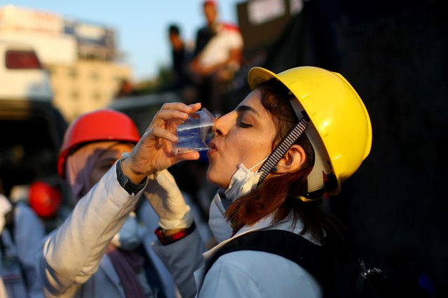 An Iraqi medical staff member drinks water during ongoing anti-government protests, in Baghdad, Iraq on November 1, 2019. (Photo by Ahmed Jadallah/Reuters)
