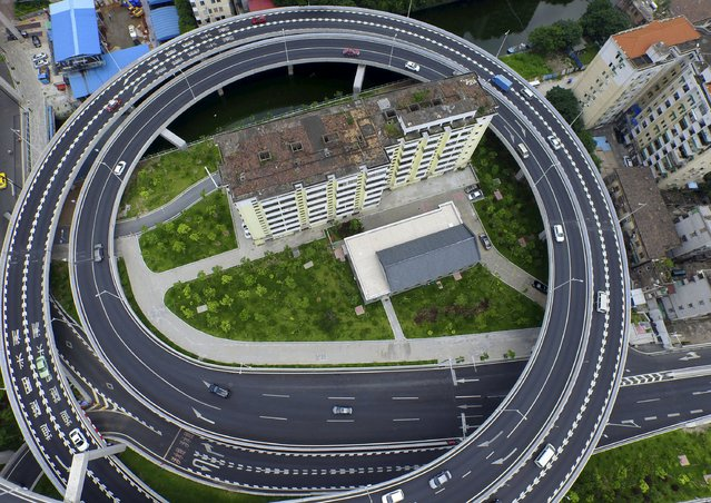 An old residential building is seen surrounded by a newly-built ring viaduct, in Guangzhou, Guangdong province, China, June 18, 2015. The building was planned to be demolished, but several units in the building refused to move out as they couldn't reach a compensation agreement with the authority, local media reported. (Photo by Ma Qiang/Reuters/Southern Metropolis Daily)