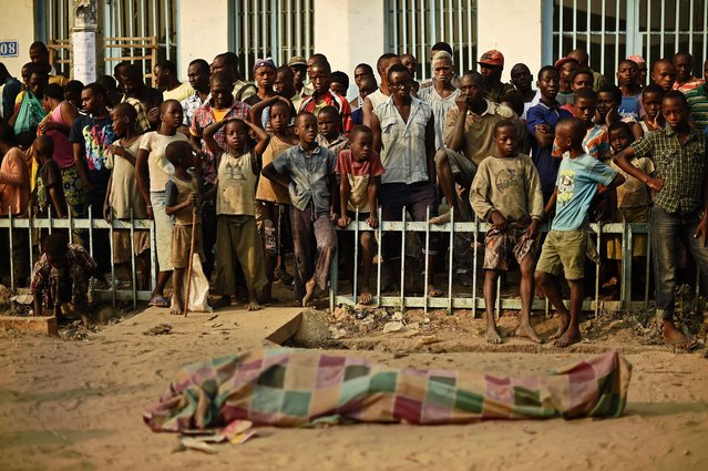 Children gather to look at a body, locals saying was a victim of a robbery, in the Kinama neighbourhood of Bujumbura on July 22, 2015. Vote counting was underway in Burundi July 22, the day after a presidential election marred by violence and international condemnation that is expected to see incumbent Pierre Nkurunziza win a controversial third term. (Photo by Carl De Souza/AFP Photo)
