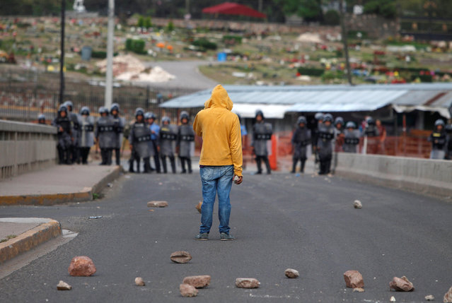 A student stands near policemen blocking a street during a protest against the education reform proposed by the government in Tegucigalpa, Honduras, May 26, 2016. (Photo by Jorge Cabrera/Reuters)