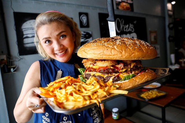 A woman holds up what the Chris Steaks & Burgers restaurant says is Thailand's biggest burger weighing more than 6 kilograms, before a competition held to eat it at the restaurant in Bangkok, Thailand, October 11, 2019. Chris Steaks and Burgers is offering a 10,000 baht ($330) prize for anyone who can finish the mammoth snack in nine minutes – one baht for every calorie. (Photo by Jiraporn Kuhakan/Reuters)