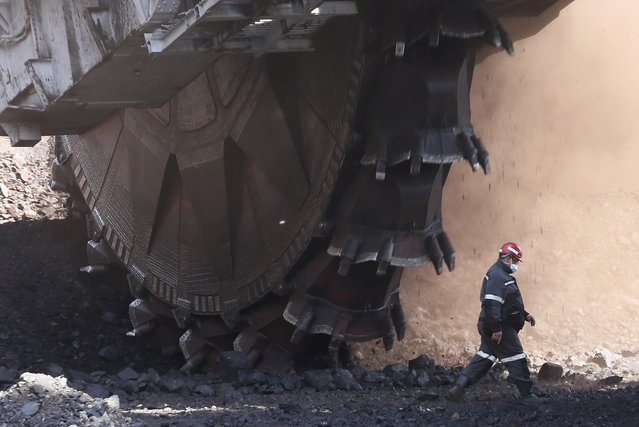 An employee walks past a Soviet-made rotary dredge with the productivity rate of 5,250 tons of processed coal a day during operations at the Beryozovsky opencast colliery, owned by the Siberian Coal Energy Company (SUEK), near the Siberian town of Sharypovo in Krasnoyarsk region, Russia, May 23, 2017. (Photo by Ilya Naymushin/Reuters)