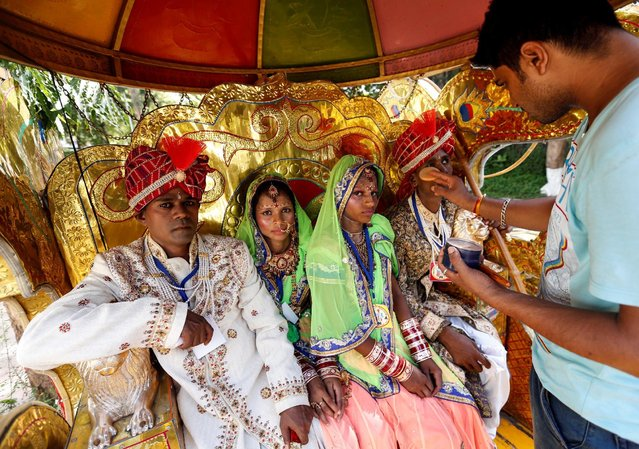 A groom gets his make-up done in a horse cart during a mass wedding ceremony organised for underprivileged and physically challenged couples in Mumbai, India, May 29, 2016. (Photo by Danish Siddiqui/Reuters)