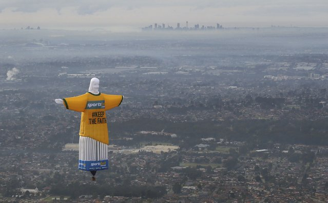 """A hot air balloon in the shape of Brazil's Christ the Redeemer statue flies over the Sydney skyline June 12, 2014. The balloon, measuring over 45 metres tall and built in Britain, flew over the Sydney skyline on Thursday to publicise an online sports betting agency, asking fans of Australia's national soccer team """"Socceroos"""" to 'keep the faith' as they compete in the 2014 World Cup in Brazil. (Photo by David Callow/Reuters)"""
