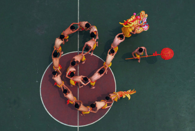 Students learn to perform a dragon dance under the instruction of a local artist at a playground in Chongqing, China, May 30, 2016. (Photo by Reuters/Stringer)
