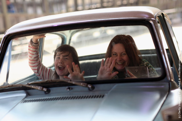 A woman and her daughter have their picture taken inside the Ford Anglia that was used in 'Harry Potter and the Chamber of Secrets' (the second film in the series) at the new Harry Potter Studio Tour at Warner Brothers Leavesden Studios