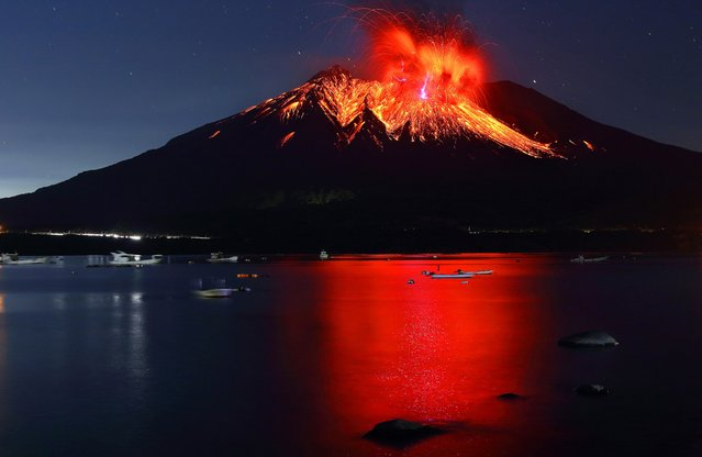 """""""Sakurajima volcano is as isolated as Mt. Fuji, making it hard to grasp the scale, as there are no nearby mountains for comparison. However, looking from the opposite shore, the height of the mountain topping 3,600 feet, the scale of the pillar of fire spewing from its top, and the beauty of the eruption reflected on the water bring fresh amazement"""". – Takehito Miyatake. (Photo by Takehito Miyatake/Steven Kasher Gallery)"""