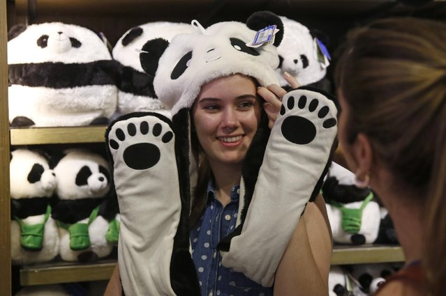 A visitor poses for a photo as she wears panda souvenirs at the shop at Ocean Park in Hong Kong, Tuesday, July 28, 2015. (Photo by Kin Cheung/AP Photo)