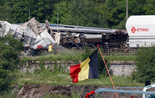 An official inspects the wreckage of a passenger train after it crashed into the back of a freight train as a barge with a Belgian flag drives past, in the eastern Belgian municipality of Saint-Georges-Sur-Meuse, June 6, 2016. (Photo by Francois Lenoir/Reuters)