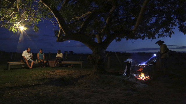 """In this May 17, 2017 photo, cowboys chat as they eat a """"churrasco"""", or barbecue, at a ranch in Corumba, in the Pantanal wetlands of Mato Grosso do Sul state, Brazil. Each day, the men and animals traverse about 11 miles from dawn until 3 p.m., in temperatures averaging about 90 degrees Fahrenheit during the day. (Photo by Eraldo Peres/AP Photo)"""