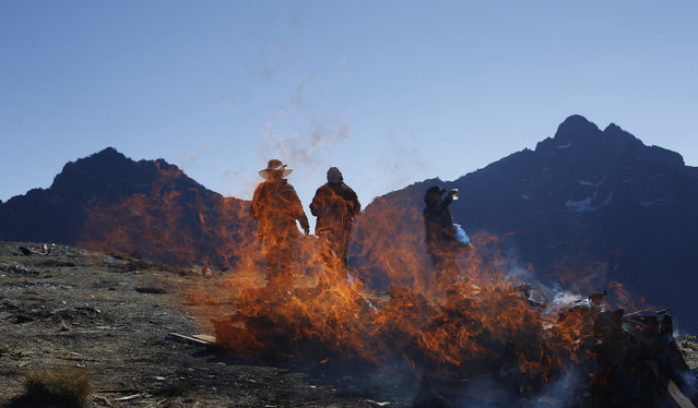 "People burn offerings to ""Pachamama"", or Mother Earth, and ask for good fortune on La Cumbre, a mountain that is considered sacred ground, on the outskirts of La Paz, Bolivia, Saturday, August 1, 2015. (Photo by Juan Karita/AP Photo)"