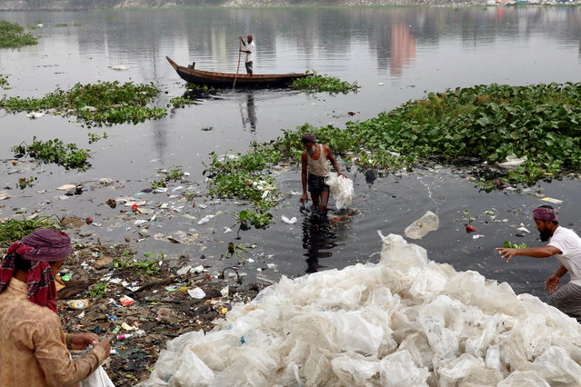 Men wash plastic waste in the waters of the Buriganga river before recycling it, in Dhaka, Bangladesh, October 23, 2019. (Photo by Mohammad Ponir Hossain/Reuters)
