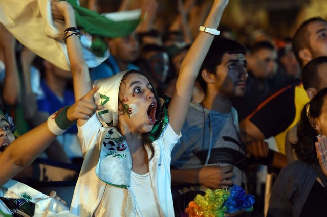 Algerian fans celebrate in Algiers on June 26, 2014 after Algeria eliminated Russia with a 1-1 draw in a FIFA 2014 World Cup Group H match. (Photo by Farouk Batiche/AFP Photo)