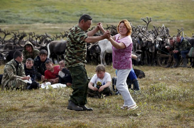 People dance during a ceremony to mark Reindeer Day at a camping ground, some 200 km (124 miles) northeast of Naryan-Mar, the administrative centre of Nenets Autonomous Area, far northern Russia, August 2, 2015. (Photo by Sergei Karpukhin/Reuters)