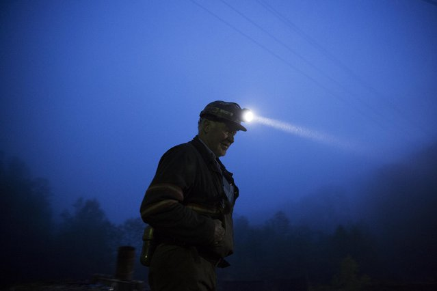 """In this Thursday, May 12, 2016 photo, coal miner Scott Tiller prepares to head into an underground mine less than 40-inches high at dusk in Welch, W.Va. """"I don't think we're the cause of any climate change"""", said Tiller. """"Maybe somewhat but look at all these millions of automobiles running around putting out carbon, nobody's trying to stop them"""". (Photo by David Goldman/AP Photo)"""