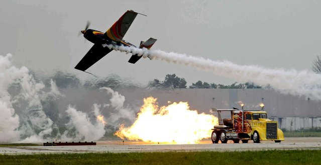 Patty Wagstaff flies by the Shockwave truck during the Dayton air show on Saturday, June 28, 2014, in Dayton, Ohio. (Photo by Ty Greenlees/AP Photo/The Dayton Daily News)