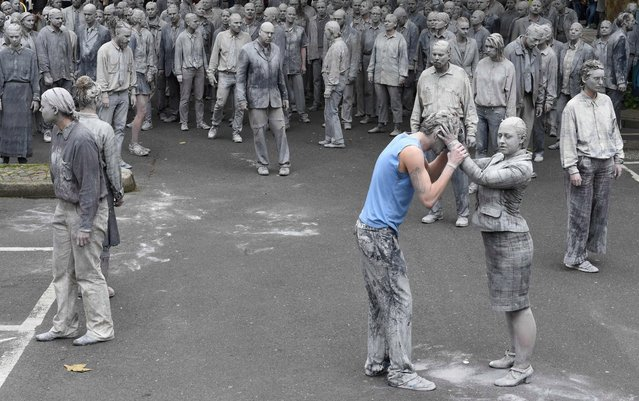 """Performer smeared with clay demonstrate during the art action """"1000 Gestalten"""" on July 5, 2017, on a street in Hamburg, northern Germany, where leaders of the world's top economies will gather for a G20 summit. More than 100,000 anti-capitalist demonstrators, including several thousand leftwing extremists, are expected to descend on the Hanseatic city ahead of the two-day summit which opens on Friday, July 7, 2017. (Photo by Christof Stache/AFP Photo)"""
