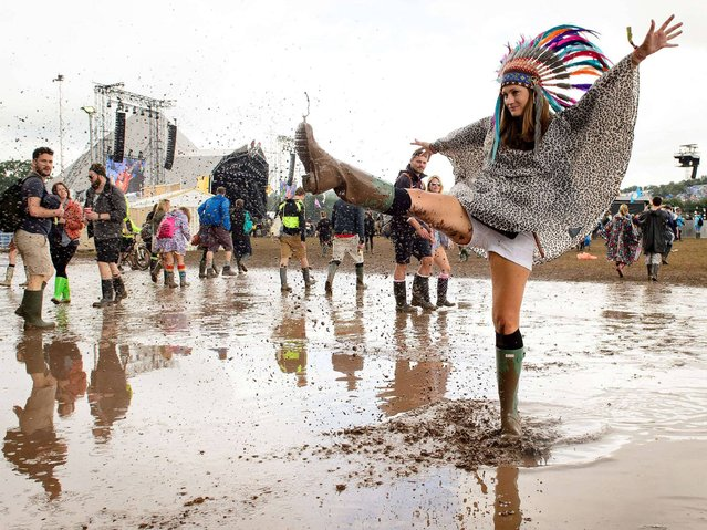 A woman kicks water in a puddle as she poses for photographers, on the first official day of the Glastonbury Festival of Music and Performing Arts on Worthy Farm in Somerset, south west England, on June 27, 2014. (Photo by Leon Neal/AFP Photo)