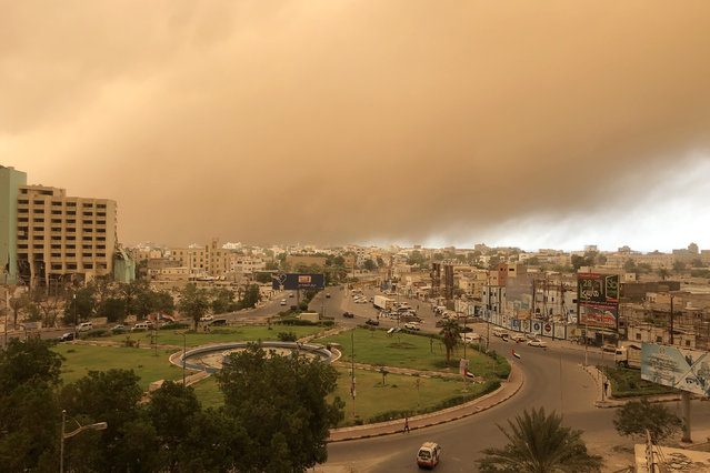 A sand storm approaches Yemen's second city of Aden on September 11, 2019. (Photo by Nabil Hasan/AFP Photo)