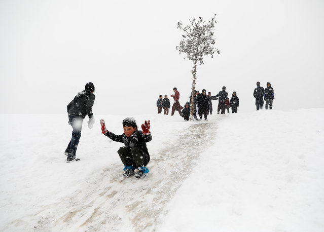 Afghan boys slide down a snow-covered slope in Kabul, Afghanistan on January 6, 2020. (Photo by Mohammad Ismail/Reuters)