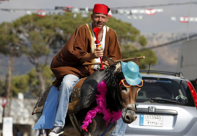 A man rides a donkey during a donkey race in Roum village, Jizeen countryside, southern Lebanon, August 9, 2015. (Photo by Ali Hashisho/Reuters)