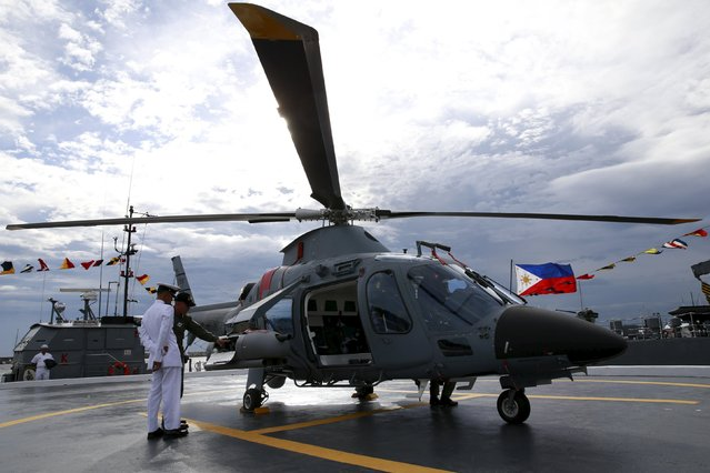 Members of the Philippine Navy inspect one of the two newly-acquired AW109E multi-purpose helicopter during a ceremony at the Philippine Navy headquarters in Manila August 10, 2015. The Philippines acquired two AW109 helicopters, which the navy armed with machine guns and rockets to support amphibious landing operations by local marines. (Photo by Romeo Ranoco/Reuters)