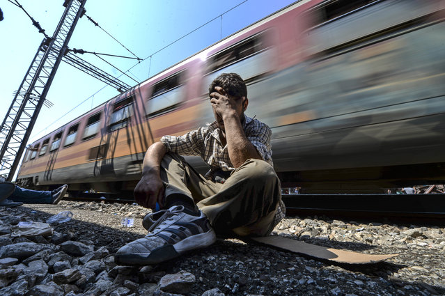 An exhausted and frustated migrant holds his head after he missed to get a place on a train heading to the Serbian border at the train station in Gevgelija, The Former Yugoslav Republic of Macedonia, August 13, 2015. (Photo by Georgi Licovski/EPA)