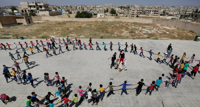 """Students form a circle as they play during a celebration marking the end of the school year, at """"Syria, The Hope"""" school on the outskirts of the rebel-controlled area of Maaret al-Numan town, in Idlib province, Syria June 1, 2016. (Photo by Khalil Ashawi/Reuters)"""