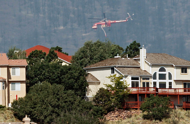 A firefighting helicopter flies over homes while battling the Waldo Canyon wildfire west of Colorado Springs, on June 27, 2012. (AP Photo/Ed Andrieski)
