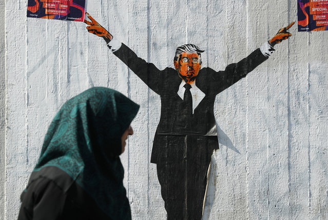 A Muslim woman walks past a street artist's rendition of U.S. President Donald Trump on June 27, 2017 in Berlin, Germany. The U.S. Supreme Court recently partially lifted a blockade by lower courts of Trump's travel ban on people from six predominantly Muslim countries, though the court decision allows people with a viable connection to the U.S., for instance through family, study or work, to still enter the U.S. (Photo by Sean Gallup/Getty Images)