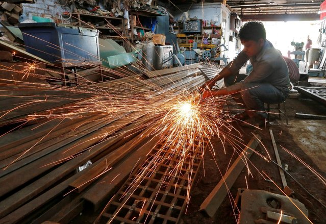 A worker grinds a metal gate inside a household furniture manufacturing factory in Ahmedabad, India, July 1, 2016. (Photo by Amit Dave/Reuters)