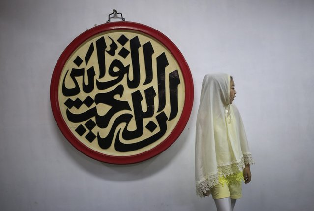 A Muslim girls is seen in the prayer hall of Niujie Mosque after prayers for Eid al-Fitr in Beijing, China, 06 July 2016. Muslims around the world celebrate the Eid al-Fitr festival, which marks the end of the Muslim fasting month of Ramadan, starting 06 July, and is celebrated with prayers, readings from the Koran, and gatherings with family and friends. (Photo by How Hwee Young/EPA)