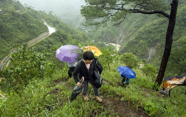 Stranded commuters hike up a mountain after a portion of Kennon Road was damaged by a landslide caused by Typhoon Goni in Baguio city in northern Philippines August 22, 2015. (Photo by Harley Palangchao/Reuters)