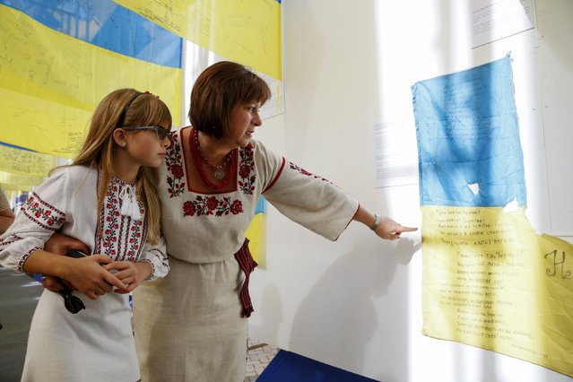 Ukrainian Finance Minister Natalie Jaresko (R), accompanied by her daughter, visits an exhibition of flags, brought from eastern regions of the country, where military conflict is taking place, during a ceremony marking the Day of the State Flag on the eve of the Independence Day in Kiev, Ukraine, August 23, 2015. (Photo by Valentyn Ogirenko/Reuters)
