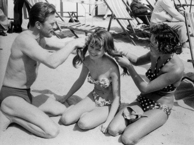 American actor Kirk Douglas and French actress Brigitte Bardot (centre) at the beach during the Cannes Film Festival, April 1953. (Photo by Patrick Morin/RDA/Getty Images)