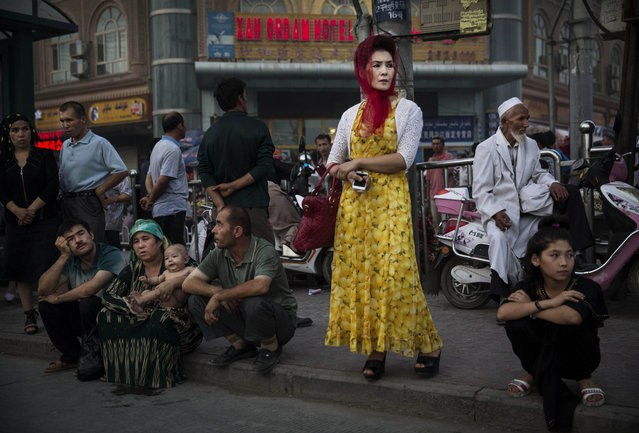 Uyghurs wait at a bus stop on July 27, 2014 in old Kashgar, Xinjiang Province, China. (Photo by Kevin Frayer/Getty Images)