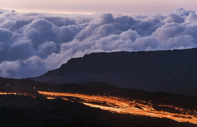 Molten lava flows from the Piton de la Fournaise, one of the world's most active volcanoes, at dawn on the French Indian Ocean Reunion Island, August 25, 2015. The eruption which started on Monday is the fourth one this year for the Piton de la Fournaise, sending hot jets of molten lava spewing up from the peak. (Photo by Gilles Adt/Reuters)