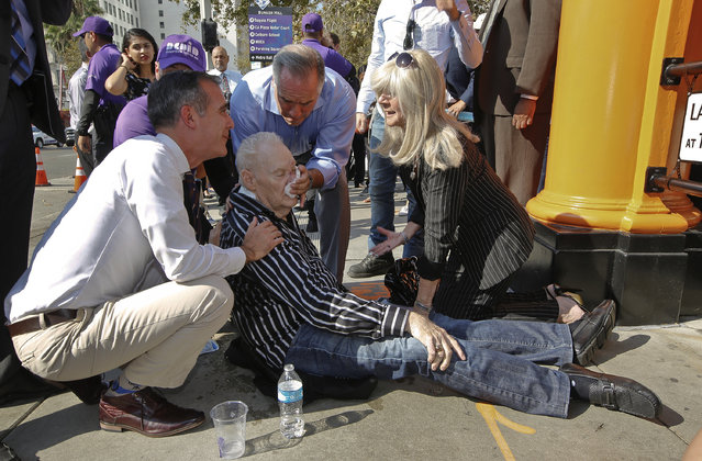 Los Angeles Mayor Eric Garcetti, left, comes to the aid of an unidentified man who collapsed in downtown Los Angeles Thursday, August 31, 2017. The temperature in downtown Los Angeles shot past 90 degrees early in the day and a spectator collapsed just as Mayor Eric Garcetti was about to start a late-morning ceremony to mark the reopening of the city's historic Angels Flight funicular railroad. The man appeared to recover but was taken away by paramedics. (Photo by Damian Dovarganes/AP Photo)