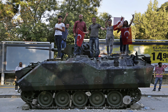 Turkish citizens stand on a damaged Turkish military APC that was attacked by protesters in a street near the Turkish military headquarters in Ankara, Turkey, Saturday, July 16, 2016. (Photo by Hussein Malla/AP Photo)