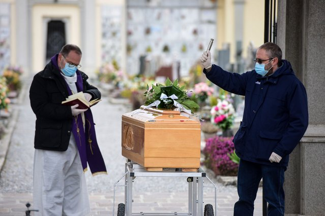A pallbearer (R) helps a priest (L), both wearing a face mask, give the last blessing to a coffin during a funeral service at the cemetery of Bolgare, Lombardy, on March 23, 2020 during the COVID-19 new coronavirus pandemic. (Photo by Piero Cruciatti/AFP Photo)