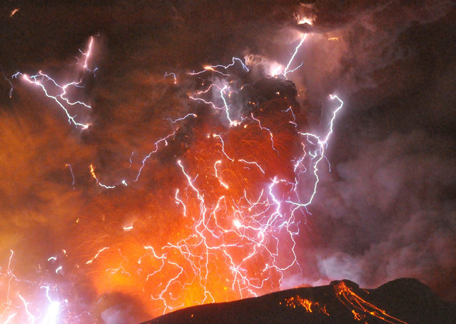 Volcanic lightning or a dirty thunderstorm is seen above Shinmoedake peak as it erupts, between Miyazaki and Kagoshima prefectures, in this photo taken from Kirishima city and released by Minami-Nippon Shimbun January 28, 2011. (Photo by Reuters/Minami-Nippon Shimbun)