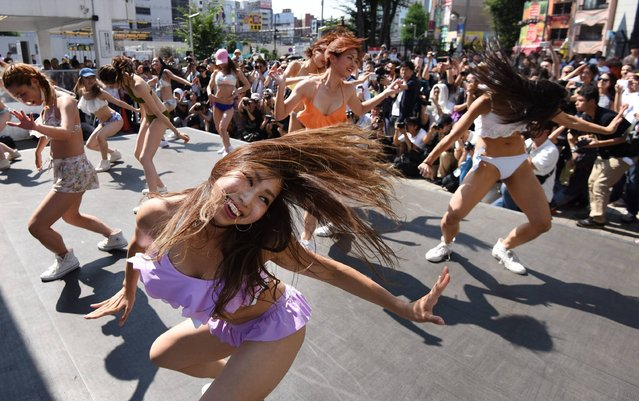 Dancers wearing new bikinis perform in front of passers-by and a line of photographers during a promotional flash mob event on a square outside Shinjuku station in Tokyo on July 18, 2016. The event was organized by the Japan Swimsuit Association to promote new swimwear. (Photo by Toru Yamanaka/AFP Photo)