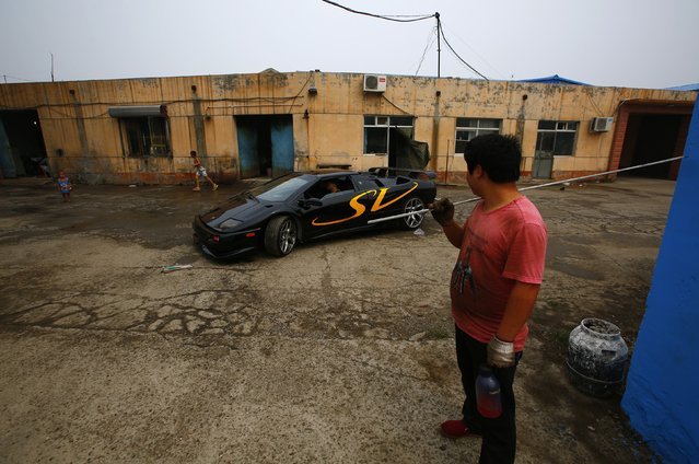 A man looks on as Wang Yu (C) drives a handmade replica of Lamborghini Diablo out of a garage on the outskirts of Beijing, August 21, 2014. (Photo by Petar Kujundzic/Reuters)