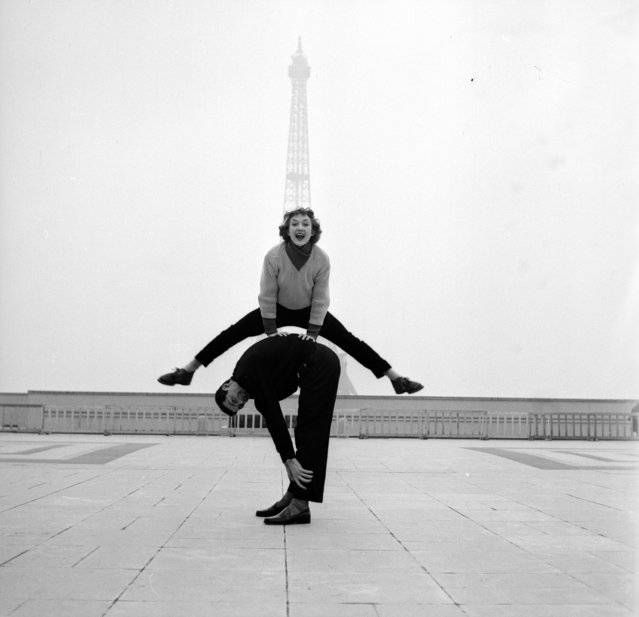 Paris street performers Jean Louis Bert and Grethe Bulow playing leap-frog in front of the Eiffel Tower, 1955.  (Photo by Jean Berton)